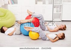Relaxing after workout - woman and kids resting on the floor with large gymnastic balls