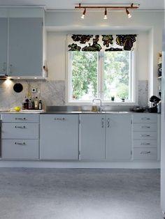 rideau cuisine enrouleur en blanc à motifs feuilles vertes comme accent dans la cuisine gris clair