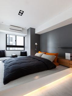 I like the modern look of this bedroom, especially the rich gray wall color with the bright orange pillows.