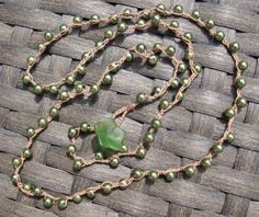 These are pretty glass faux pearls in an olive green color. This chain is made from thin cotton thread, not as thick as the cording. I used a glass flower and loop for the clasp.