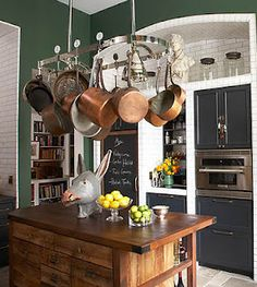 A Green Kitchen. In the Manhattan kitchen of Bronson van Wyck, an Urban Archaeology pot rack hangs over an island made of salvaged pine; the appliances are by Electrolux. Green Kitchen Walls, Dark Green Kitchen, Dark Green Walls, Kitchen Paint, New Kitchen, Kitchen Ideas, Copper Kitchen, Kitchen Small, Eclectic Kitchen