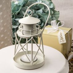 Lighthouse Luminous Metal Lantern From Fashioncraft- Guide your guests safely to their tables with these classic little metal lighthouse lanterns. They will create a lovely warm ambiance in your event hall when they glow with tealight candles.