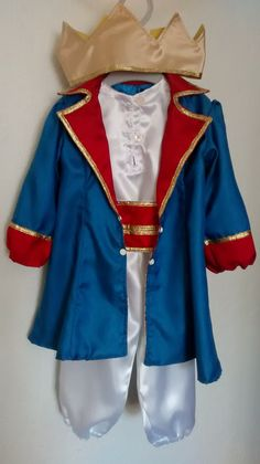 Fantasia Pequeno Príncipe Luxo para crianças com 1 ano de idade. Faça a festa de um aninho do seu filho com o tema Pequeno Príncipe. A fantasia é composta por uma regata branca, uma calça branca, um cinto vermelho e dourado, um casaco azul e vermelho, e uma coroa dourada, todos feitos em ceti...