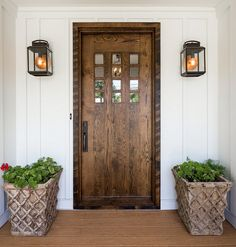 Farmhouse front door. White board and batten farmhouse exterior with wood front…