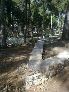Detalle de esquina del muro escalonado con jardín de rocalla al fondo.