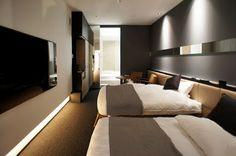 コリドールを抜けると寝室。壁には70インチはありそうなテレビ。奥にバスルームへと続く。japan-architects.com