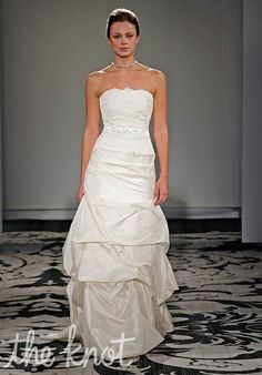 Gown features ruched bodice, detachable belt, lace bustier, and pick-up skirt.