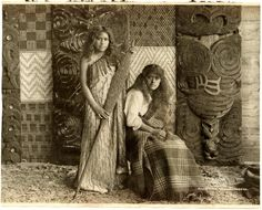 Photograph (black and white) from an album; portrait of two Maori women; one standing wearing a korowai (tag cloak), holding a hoe (canoe paddle) with shell inlay; the other girl is Mairie seated wearing western-style blouse and blanket; backdrop of tukutuku panels (of woven reeds) and poupou (carved house panels) with shell inlay; Whakarewarewa, New Zealand.  Photogravure