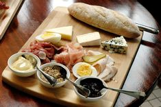 The Ploughman's Platter, a selection of blue cheese, Gruyere and brie, with pork, ham, beef and turkey pastrami, served with a freshly baked baguette, beautifully laid out on a wooden chopping board.
