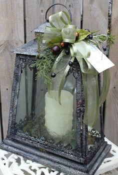 Lantern centerpiece with LED candle and ribbons on top.