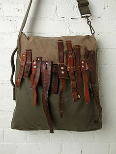 Distressed canvas hobo bag with flap closure and multi-buckle strap detailing on front of flap.
