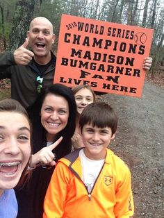 "Tim Hudson and family pose for a photo with a ""MADISON BUMGARNER FAN LIVES HERE"" poster! As you probably know, Bumgarner moved in with the Hudson family when his lease ran out. The Bumgarners live in the basement of the Hudson house!"