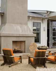 Relaxing outdoor fireplace. Designer: Jean Larette. Photo: Reed Davis. housebeautiful.com #tangerinetango #brightorange