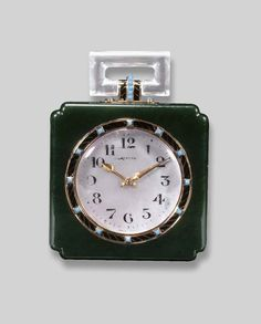 A JADE AND MOTHER-OF-PEARL TABLE CLOCK, BY CARTIER The circular mother-of-pearl dial with Arabic numerals and black enamel and turquoise collet bezel to the jade clock and rock crystal handle, circa 1930