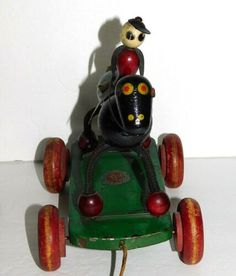 It is a wooden and wood beaded, black race horse and jockey. The jockey has cutout tin arms and legs.