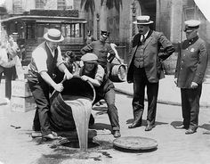 New York City Deputy Police Commissioner John A. Leach, right, watching agents pour liquor into sewer following a raid, ca 1921  (From www-tc.pbs.org )