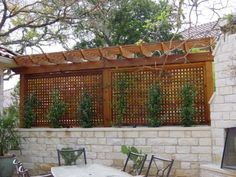 Privacy fences and enclosures don't need to be ugly. Combined with a stone wall, planter and small pergola/arbor structure, this privacy screen is a backyard focal point.