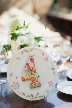 Thrift store plate with fabric covered table number is easy DIY