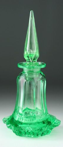 A molded green uranium glass dressing table bottle with a hollow spire stopper, six sided facet body, and outswept wavy edge skirt. c. 1900