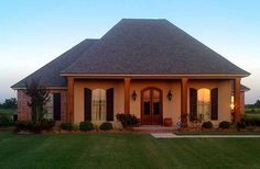 Architectural Designs Acadian Style House Plan 56349SM looks great at dusk! 3 beds, 2 baths, just under 3,000 square feet.