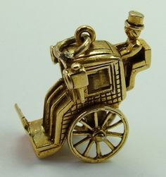 A large 1960s English 9ct gold charm of a hansom cab with moving wheels, hallmarked for 1964.