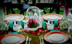 Fresh flowers under a glass cloche provide the centerpiece for a lovely yet whimsical tablescape that provides lots of little details and colors to catch the eye. Special event, dinner party, wedding reception, birthday party, anniversary party.