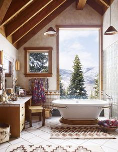 The tub in the master bath of this Utah home is by Kohler, the stool was made by a local craftsman, and the Navajo rugs are from 1910; the copper sconces and pendants are original to the house. ➤To see more Luxury Bathroom ideas visit us at www.luxurybathrooms.eu #luxurybathrooms #homedecorideas #bathroomideas @BathroomsLuxury