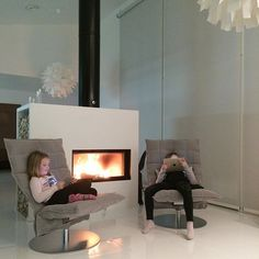 Woodnotes Swivel k Chairs, narrow, upholstered with Sand paper yarn cotton fabric. Modern Scandinavian style living room with a fireplace.