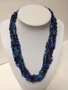 "Check my blog: http://centraltexascrafter.com/handcrafted-necklaces/ or direct link below.  Want the look of beads but enjoy the light-weight feel of yarn? Handcrafted, glittery and expandable deep blues and purple necklace. Length can be adjusted from 18"" to 24"" with ease. No metal, no clasps - easy to put on and wear. You'll get so many comments on your ""beads"" - this unique necklace will garner you many compliments!"