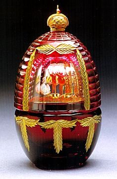 "(3) FABERGE eggs__Theo ___Fabergé, Imperial Egg ""Encore"" Rich cranberry colored lead crystal is hand carved in an intricate web pattern, offset by seven golden swags. The curtain opens upon turning the crown to reveal the surprise, the Pas de Deux from the ballet Swan Lake.  The silver Swan exits the stage as the crown is rotated to float to a secret lagoon painted on the reverse."