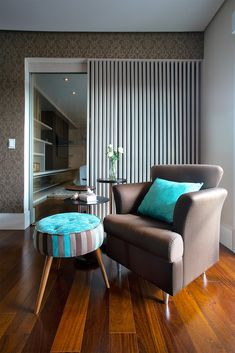 espaço de leitura do quarto do casal decorado em marrom e azul turquesa. as ripas de madeira separam o quarto do closet dele.