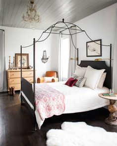 The pine-clad ceiling in singer-songwriter Holly Williams' bedroom is painted a cloudy gray. The star of the room—a wrought- iron canopy bed from Restoration Hardware—is a close match to an antique one that belonged to her maternal grandmother. To toughen up the otherwise feminine space, Holly brought in a rustic leather club chair and simple pine chest. Brass sconces cast a warm light while keeping tabletops clear.   - CountryLiving.com
