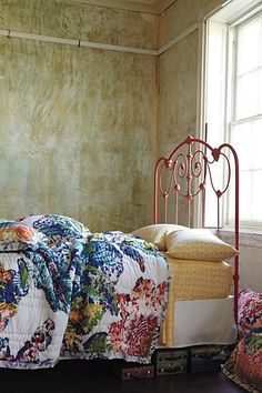 I love this brightly-colored quilt with the yellow print sheets.  And the red bed-frame!  Wow!
