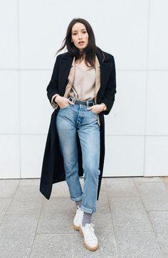 Street style look blusa bege, calça jeans, tênis branco e sobretudo preto.
