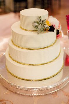 Simple wedding cake. Touches of gold with natural flowers.