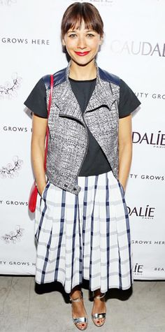 MARCH 15, 2014  WHAT SHE WORE At the grand opening of the Caudalie Boutique Spa, Rashida Jones stepped out in pretty windowpane-print midi skirt, dressing it down (and revving up the cool factor) with a black tee and moto vest, and styled with a bright red cross-body purse (to match her lip) and silver sandals.