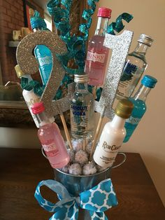 21st birthday alcohol bouquet! Hot glue holds the bottles to the spikes well. Put rocks in base because arrangement is top heavy.