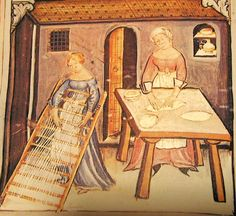 Women making pasta. Note the aprons and turned-up bugle cuffs, as well as the turban-like veil worn by the woman at right.