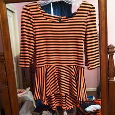 Striped peplum top Coral and black stripes. Zipper on back. Elbow length sleeves. 95% polyester and 5% spandex. Never worn, no tags. Loops at waist for thin belt. 24 inches long spoiled Tops