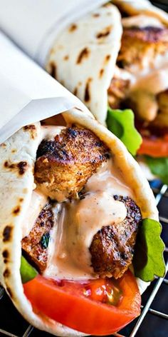 Seasoned lemon chicken grilled to perfection and wrapped in soft and chewy flatbread with arugula greens, fresh tomatoes, and spicy garlic sauce.
