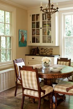 "Breakfast Room from thecottagejournal.com, ""A glass-door cupboard and other cabinetry aren't just meant for the kitchen, as this breakfast room proves. Because these built-ins and walnut counters match those found in the kitchen, a visual connection is created between the two rooms."""