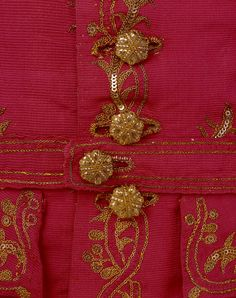 Detail, Women's Waistcoat, British,1760-69, V Museum.  Silver-gilt buttons fasten this 1760s woman's riding waistcoat of eye-catching bright pink silk. Each button has a wooden core. The indented edges form useful notches around which to secure strips of silver-gilt foil and thread. They complement an embroidered pattern of flowers worked in chain-stitched silver-gilt thread and spangles (or sequins).