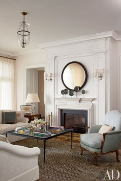 Silver-plate sconces from Remains Lighting flank the living room fireplace in a Long Island, New York, home by decorator Mariette Himes Gomez.