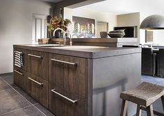 Dark varnish ikea oak front cabinets. With concrete work top and white walls