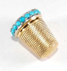 An antique gold thimble with turquoise circa 1890
