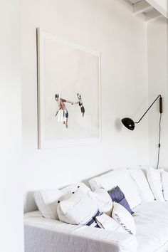 Art, black task light and white sofa in in the relaxed and light-filled L.A home of Victoria from SF Girl By Bay. Laure Joliet.