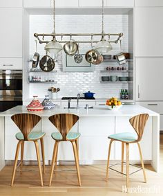 Designer Katie Ridder installed open shelves and Urban Archaeology's Industrial pot rack in a Manhattan apartment's existing kitchen to make everyday items easily accessible. The elegant barstools from Cherner Chair Company are a 1958 design by Norman Cherner and are cushioned in MK Collection's Summer Strié.
