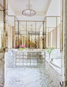A ceiling fixture by Chameleon Fine Lighting accents the master bath, which is outfitted with a mirrored vanity | archdigest.com