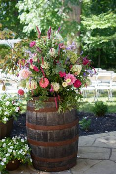 Seasonal Ohio garden flowers arranged on top of barrel for outdoor wedding ceremony.  Flowers by Buckeye Blooms; Photo by Amy Rebecca Photos.