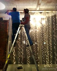 Hang a vertical string of lights from a rod and add the sheer to soften it. This would go great at the window that already has sheer window panels and a curtain rod!